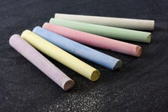 Color chalk pieces on blackboard Stock Images