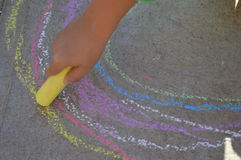 Color chalk rainwob drawing on the street. Color chalk drawing by the kid hands, showing only yellow chalk Royalty Free Stock Photo