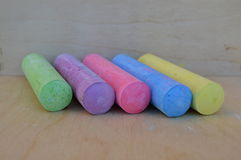 Color chalk sticks over a wood table. Set diagonally Stock Images
