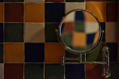 Color checkered wall. Shaving mirror on a color checkered wall Stock Photo