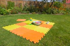 Color children`s mat on the green grass in the country close-up. Handmade sandpit. royalty free stock photo