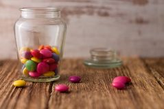Color chocolate smarties in glass dose and around on wooden board Stock Photo