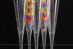 Color chocolate tablets inside the champagne glasses. On a black glass plate stock photo