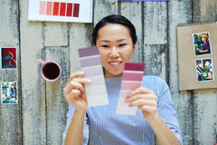 Color choice. Young designer choosing between lilac and purple color swatches Stock Photos