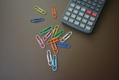 Color clips of different colors with a gray calculator on a brown matte background. Excellent bright photos for stores for articles and magazines and any glosses royalty free stock image