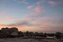 Color cloud formations at sunset over the water. With rocks Royalty Free Stock Photography
