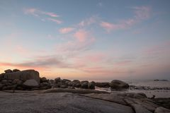 Color cloud formations at sunset over the water. With rocks stock image