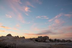 Color cloud formations at sunset with rocks. In the foreground Stock Photos