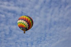 Color in the Clouds. Looking up at a colorful hot air balloon against a dappled, blue, summer sky stock photo
