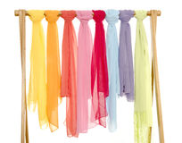 Color coordinated scarves arranged on a rack. Royalty Free Stock Image