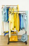 Color coordinated yellow and blue clothes on hangers. Stock Photos