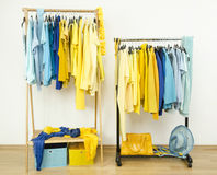 Color coordinated yellow and blue clothes on hangers. Stock Images