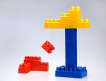 Color crane toy. Color crane carring red block Royalty Free Stock Photography