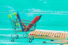 Color crayon in shopping cart on wood. Color crayon in shopping cart on vintage wood royalty free stock photo