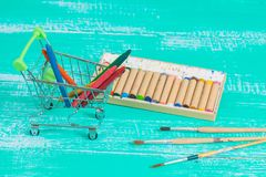 Color crayon in shopping cart on wood. Color crayon in shopping cart on vintage wood stock photo