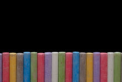 Color crayons in line. Color crayons arranged in line isolated on black Royalty Free Stock Photos