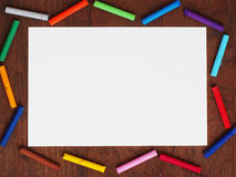 Color crayons and a paper on wooden background Stock Images
