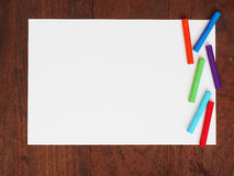 Color crayons and a paper on wooden background Stock Photo
