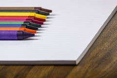 Color crayons on white paper. Color crayons on a white paper pad on the top of a desk Stock Images