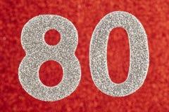 Color de la púrpura del número ochenta sobre un fondo rojo aniversario Foto de archivo libre de regalías