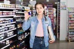 Color de las compras de la muchacha en el tarro de cristal en tienda del arte Fotografía de archivo