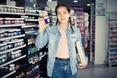 Color de las compras de la muchacha en el tarro de cristal en tienda del arte Imagen de archivo