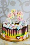 Color del arco iris de la torta del ` s de los niños en un fondo blanco con el merengue de madera Foto de archivo libre de regalías