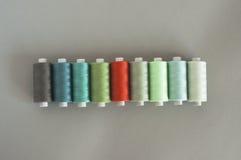 Color del hilo que pone en contraste en un fondo gris Fotos de archivo libres de regalías