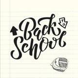 Color del negro de la mano de nuevo al texto de escuela letering en una hoja del cuaderno de la escuela con el bolso de escuela e stock de ilustración