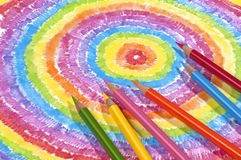 Color Drawing and Colored Pencils. Color pencils lying on a brightly colored drawing Royalty Free Stock Images