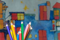 Drawing pencils on a kids drawing background. Color drawing pencils on a kids colorful houses drawing background stock photography
