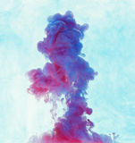 Color drop underwater creating a silk drapery. Ink swirling unde Stock Photos