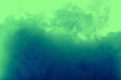 Color drop in water, photographed motion. Royalty Free Stock Image