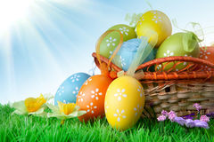 Color easter eggs in basket against blue sky and clouds Stock Photo