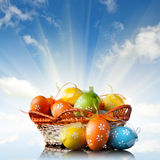 Color easter eggs in basket against blue sky and clouds. With rays of sun Royalty Free Stock Photography
