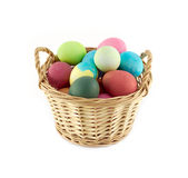 Color Easter eggs in brown basket front view isolated Royalty Free Stock Photo