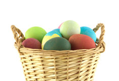 Color Easter eggs in brown basket isolated Royalty Free Stock Photo