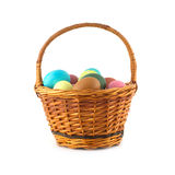 Color Easter eggs in brown basket isolated Royalty Free Stock Image