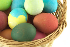 Color Easter eggs in brown basket isolated Stock Image