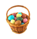 Color Easter eggs in brown basket isolated Royalty Free Stock Images