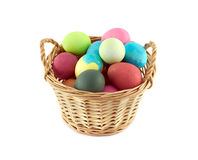 Color Easter eggs in brown basket isolated Royalty Free Stock Photography