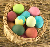 Color Easter eggs in brown basket on straw closeup Stock Image