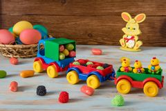 Easter toy car with trailer and color sweets in, Easter eggs, candy and bunny on wooden background. Color Easter sweets in toy track and trailers next to Color Stock Photos