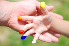 Color en las manos. cabrito y padre fotografía de archivo