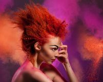 Color explosion. Beauty portrait of woman with color explosion made of color powder stock photography