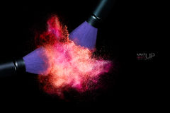 Color Explosion with Makeup Brushes Applying Powder. Isolated on. Beauty and Makeup concept. Stop action view of two makeup brushes applying matching neon pink Royalty Free Stock Image