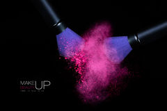 Color Explosion with Makeup Brushes Applying Powder. Isolated on. Beauty and Makeup concept. Stop action view of two makeup brushes applying matching neon pink Stock Photo