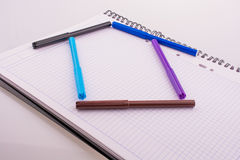 Color felt-tip pens form a house shape. On white background Stock Photos