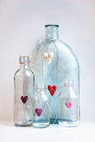 Color felted hearts in glass bottles Stock Photos