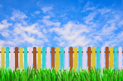 Color fence with green grass and blue sky for background Stock Photo